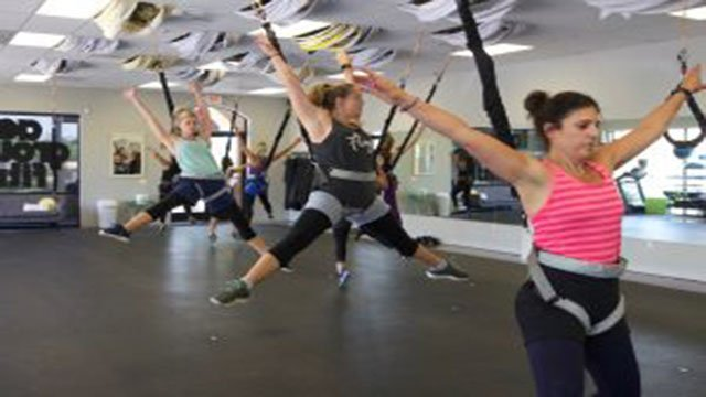 Participants in the Bungee Workout class at Tough Lotus in Chandler stretch in the air. (Source: Reinert Toft/Cronkite News)