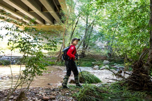 A Navajo County rescuer searches the riverbank under the bridge where one body was recovered in Tonto National Forest, Ariz., Monday, July 17, 2017. (Source: AP Photo/Angie Wang)