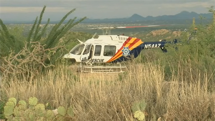 On Sunday, a police helicopter lowered a rescuer to eight hikers, including a 4-year-old boy, fastening them to a hoist that hauled them one by one to waiting rescuers on the side of the mountain creek. (Source: KOLD)