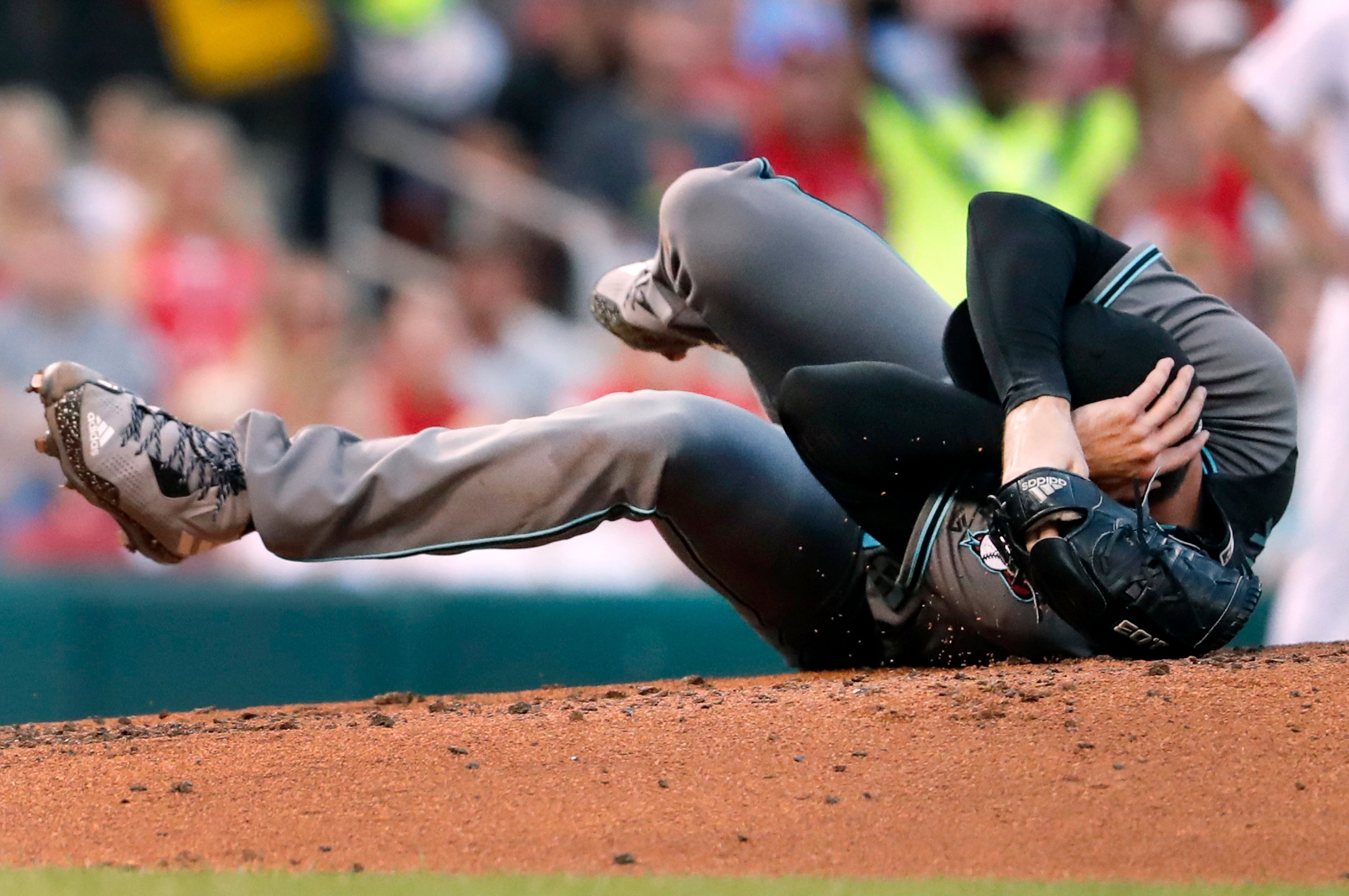 Arizona Diamondbacks starting pitcher Robbie Ray falls to the ground after being hit on the head by a ball back to the mound (AP Photo/Jeff Roberson)