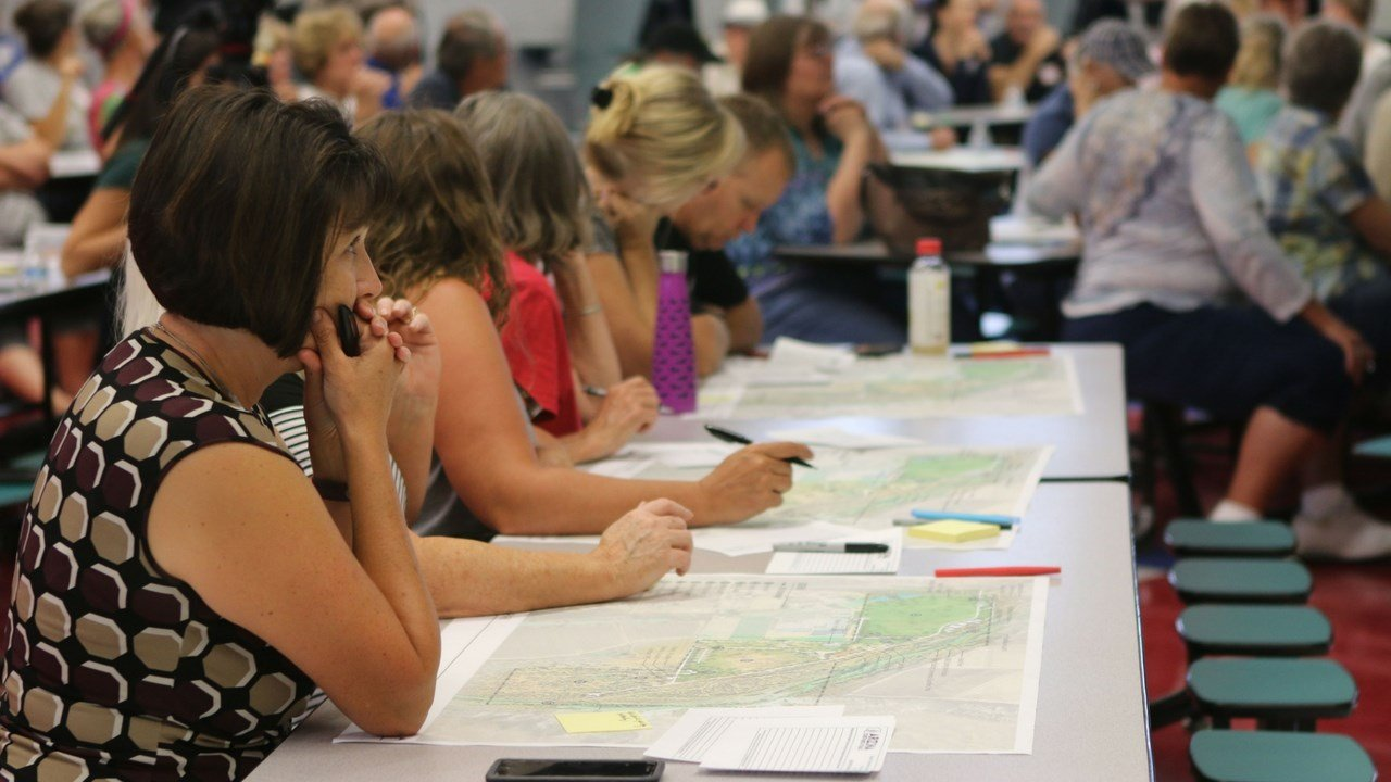 Residents looked over various site plans and listened to Arizona State Park and Trails officias discuss plans for Rockin' River Ranch at a July open house. (Photo by Alexis Kuhbander/Cronkite News)