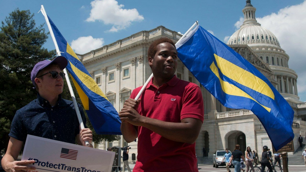 Ben Christianson, 29, and Paul Lisbon, 23, hoist equality flags over their shoulders at the Capitol where dozens of lawmakers were protesting President Donald Trump's announcement of a ban on transgender soldiers. (Photo by Megan Janetsky/Cronkite News)