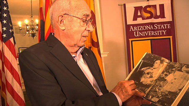 Retired Air Force Col. John Fer, who was shot down over Vietnam and held captive, thumbs through a scrapbook of the time when he was a fellow POW with Sen. John McCain, R-Arizona. (Source: Noelle Lilley/Cronkite News)