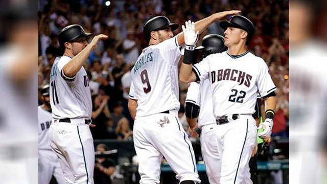 Arizona Diamondbacks' Jake Lamb (22) celebrates with Chris Iannetta (8) and A.J. Pollock (11) after hitting a grand slam during the seventh inning of a baseball game against the Los Angeles Dodgers, Tuesday. (Source: AP Photo/Matt York)