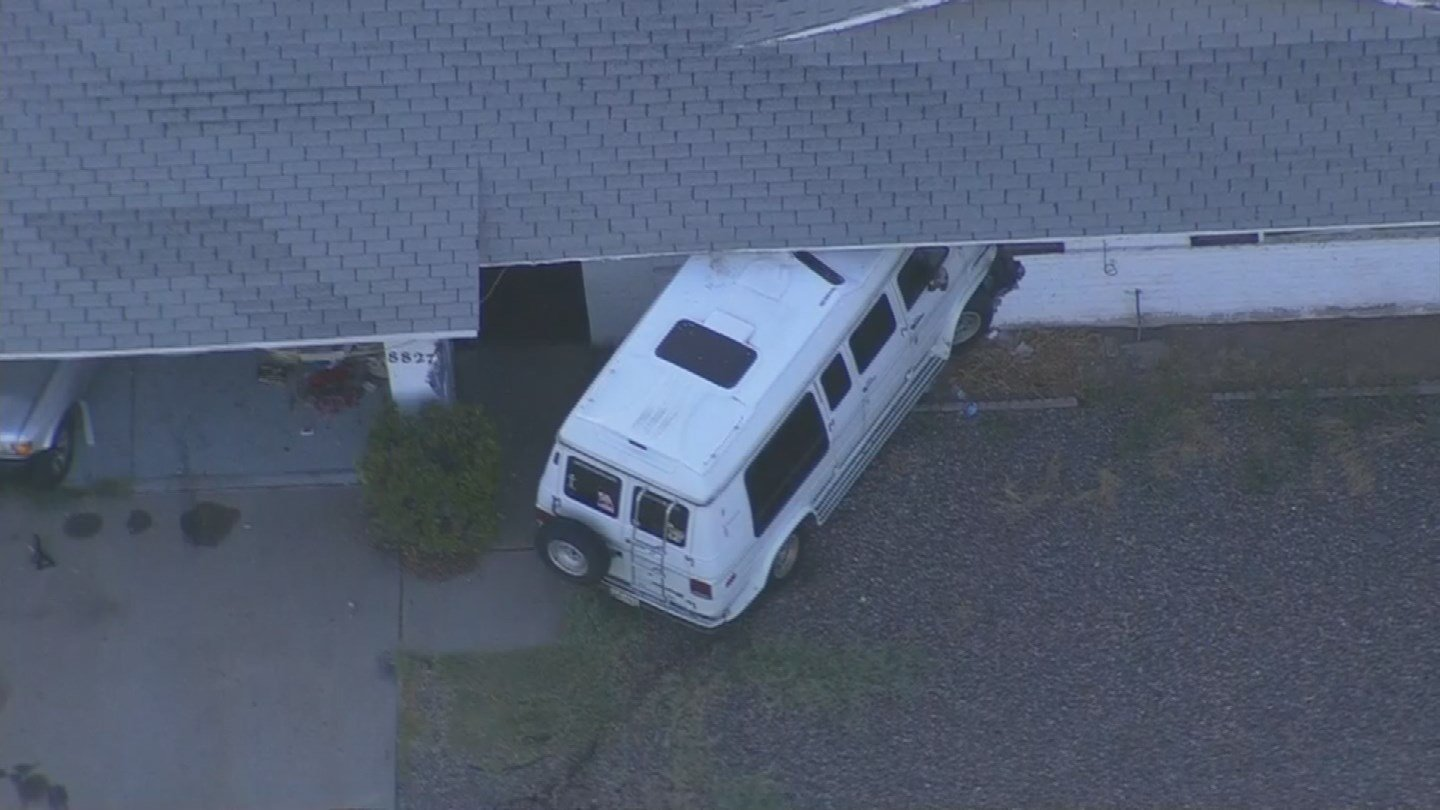 The van rammed the parked car through the garage and then proceeded to throttle the van into the front door of the home, causing extensive damage. (Source: 3TV/CBS 5)