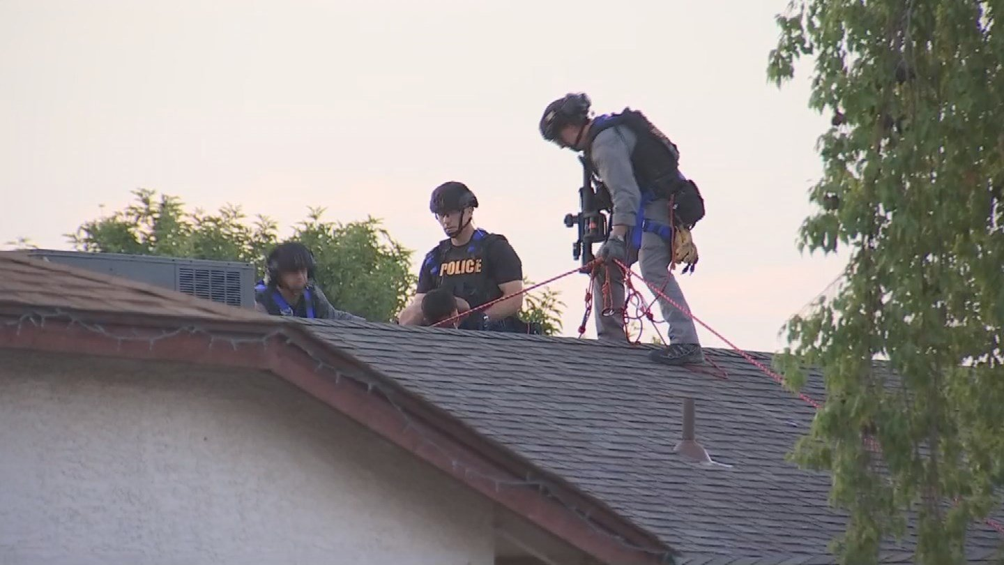 A man assaulted his mother and then fled, jumping onto the roof of a home in Phoenix, (Source: 3TV/CBS 5)