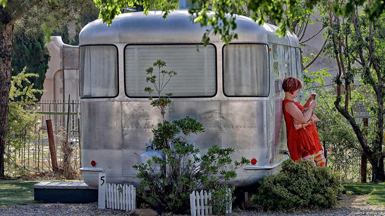 A guest takes a photo with her smartphone while leaning on a Spartan Manor travel trailer, Wednesday, April 26, 2017, at the Shady Dell Trailer Court in Bisbee, Ariz. (Source: AP Photo/Matt York)