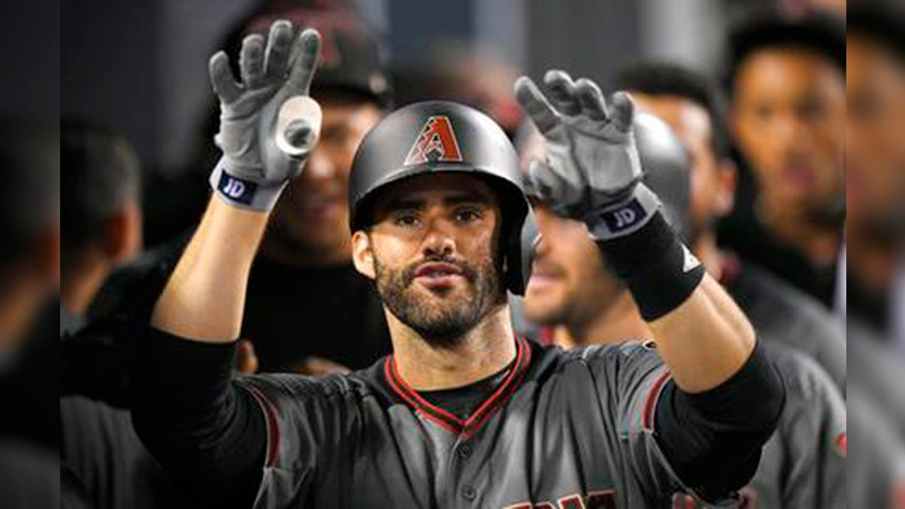 Arizona Diamondbacks' J.D. Martinez gestures toward the camera as he stands in the dugout after hitting his fourth home run of the game in the ninth inning of a baseball game against the Los Angeles Dodgers. (Source: AP Photo/Mark J. Terrill)