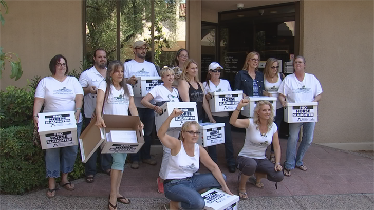 Salt River Wild Horse Management Group holding the boxes of petitions in front of Sen. Jeff Flake's office. (Source: 3TV/CBS 5)
