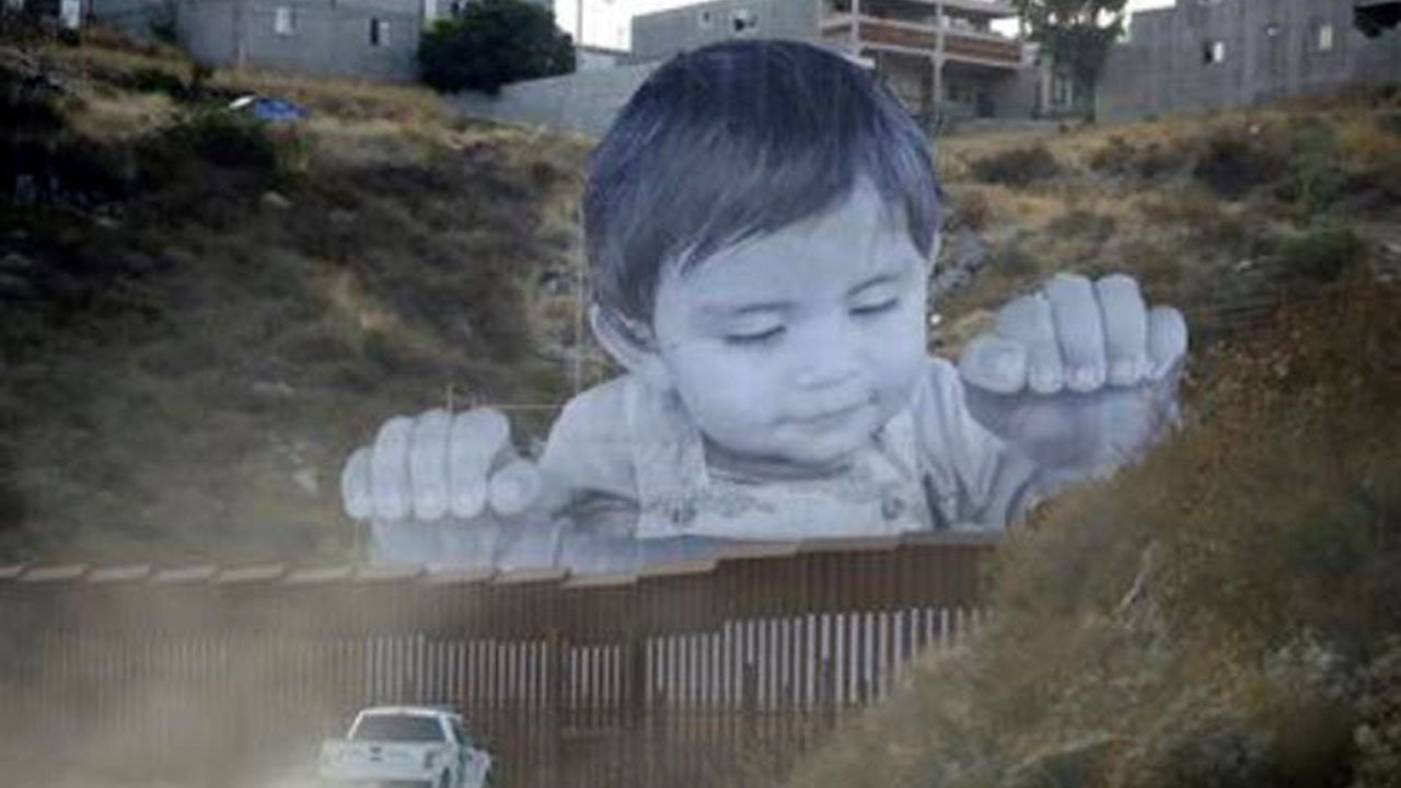 A Border Patrol vehicle drives in front of a mural in Tecate, Mexico, just beyond a border structure Friday, Sept. 8, 2017, in Tecate, Calif. A French artist aiming to prompt discussions about immigration erected a 65-foot-tall cut-out photo of a Mexican
