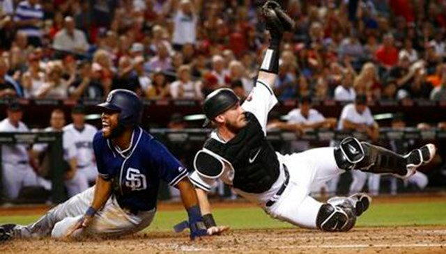 Arizona Diamondbacks' Chris Herrmann, right, shows the umpire the ball in his glove after tagging out San Diego Padres' Manuel Margot, left, as Margot tried to score during the third inning of a baseball game Sept. 8, 2017. (AP Photo/Ross D. Franklin)