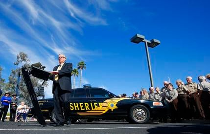 FILE - In this April 3, 2014, file photo, then Maricopa County Sheriff Joe Arpaio speaks as a volunteer pose looks on during a news conference in Sun City, Ariz. A committee of community leaders appointed by Arpaio's successor, Sheriff Paul Penzone, said