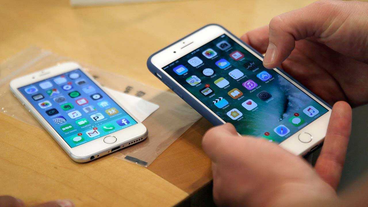In this Friday, Sept. 16, 2016, file photo, a customer sets up his new iPhone 7 Plus, right, as he switches from the iPhone 6 at a Chicago Apple Store. (Source: AP Photo/Kiichiro Sato, File)