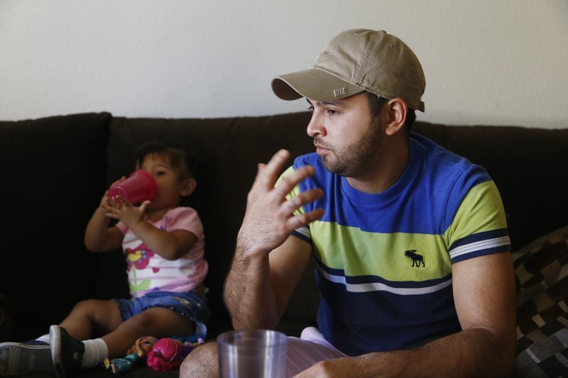 Cesar Garcia, right, talks about how he and other family members, including 1-year-old Marina, left, survived the Payson, Ariz., flash flooding this summer that killed 10 other family members, at his home. (Source: AP Photo/Ross D. Franklin)