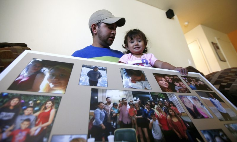 Cesar Garcia, left, talks with his 1-year-old daughter Marina, right, as they look at photographs of family members, many of whom were killed in the flash flooding in Payson, Ariz., during an interview at his home. (Source: AP Photo/Ross D. Franklin)