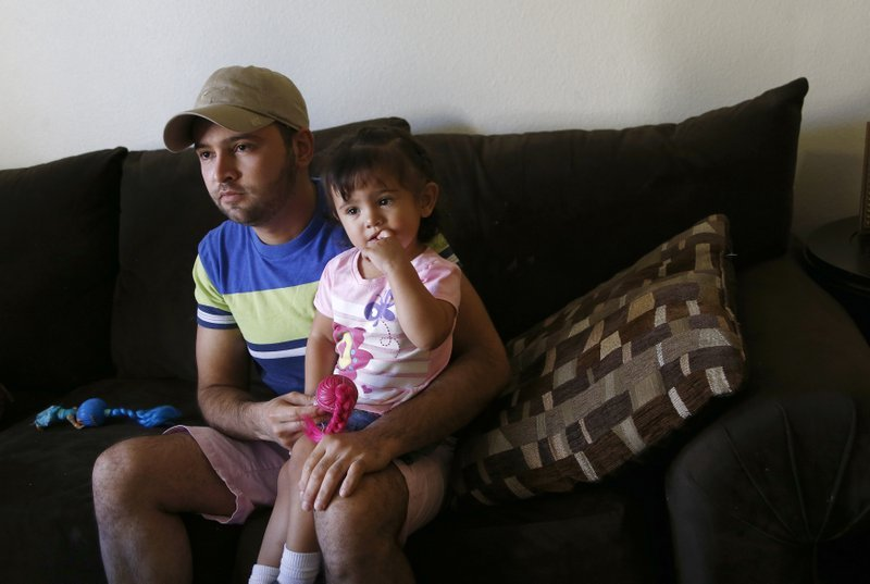 Cesar Garcia, left, sits with 1-year-old daughter Marina, as talks about how he and other family members, including Marina, survived the Payson, Ariz., flash flooding this summer that killed 10 other family members. (Source: AP Photo/Ross D. Franklin)