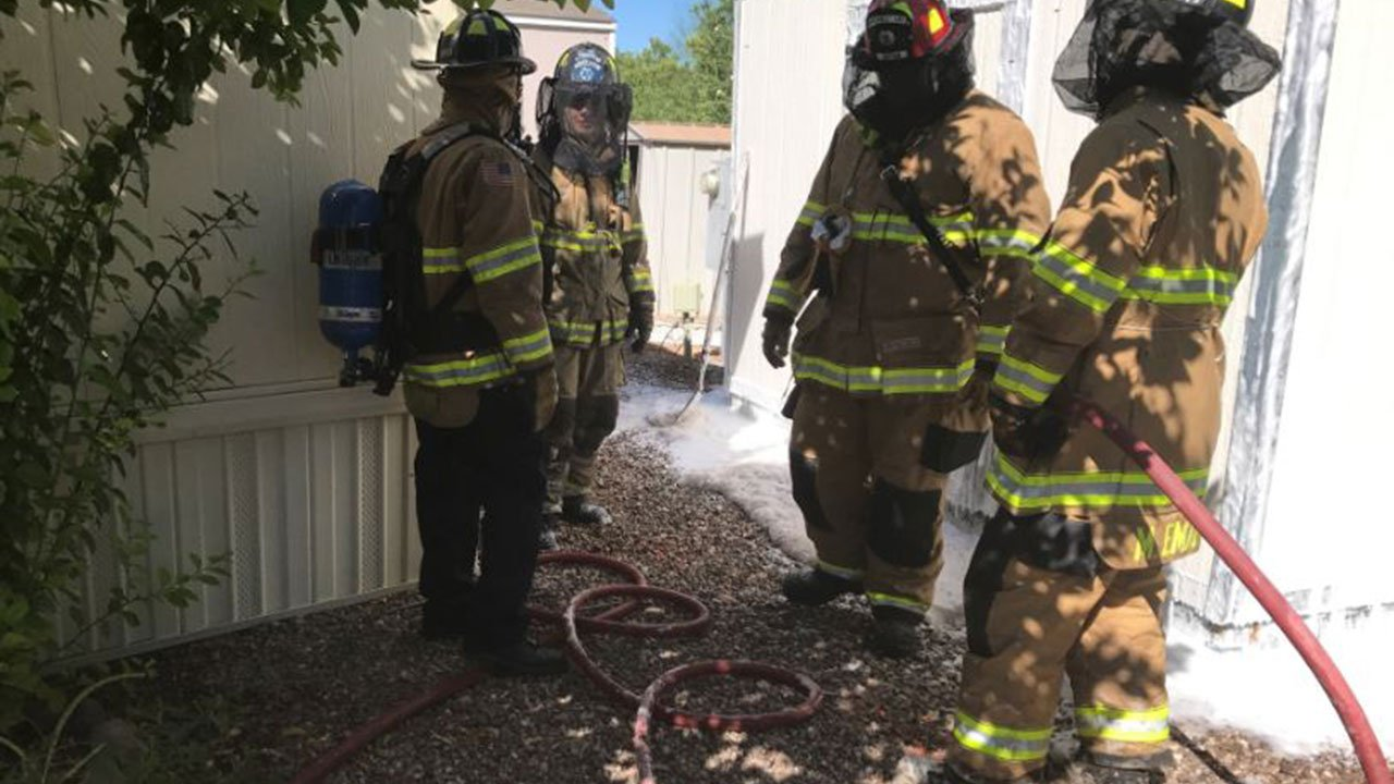 Firefighters responded in full gear, including netting, to protect themselves from a bee swarm in the 13000 block of North Sandario Road on Friday. (Source: Northwest Fire District)