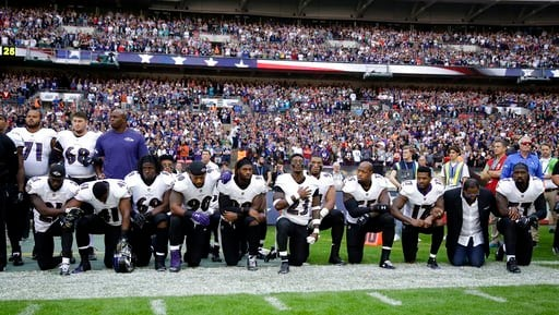 Baltimore Ravens players, including former player Ray Lewis, second from right, kneel down during the playing of the U.S. national anthem before an NFL football game against the Jacksonville Jaguars at Wembley Stadium in London. (AP Photo/Matt Dunham)