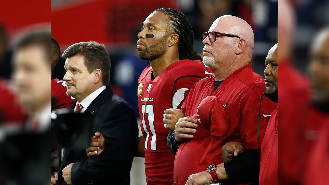 From left; Arizona Cardinals president Michael Bidwill, wide receiver Larry Fitzgerald and head coach Bruce Arians stand during the national anthem. (Source: AP Photo/Ross D. Franklin)