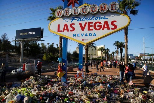 Flowers, candles and other items surround the famous Las Vegas sign at a makeshift memorial for victims of a mass shooting Monday, Oct. 9, 2017, in Las Vegas.