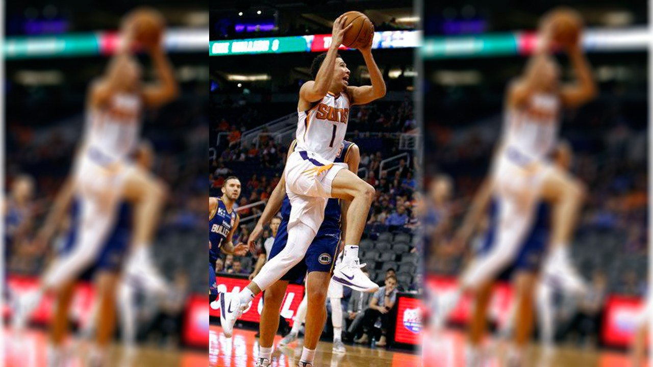 Phoenix Suns guard Devin Booker drives to the basket past Brisbane Bullets forward Daniel Kickert during the second half of an NBA basketball exhibition game against the Brisbane Bullets on Friday, Oct. 13, 2017, in Phoenix. (AP Photo/Ralph Freso)