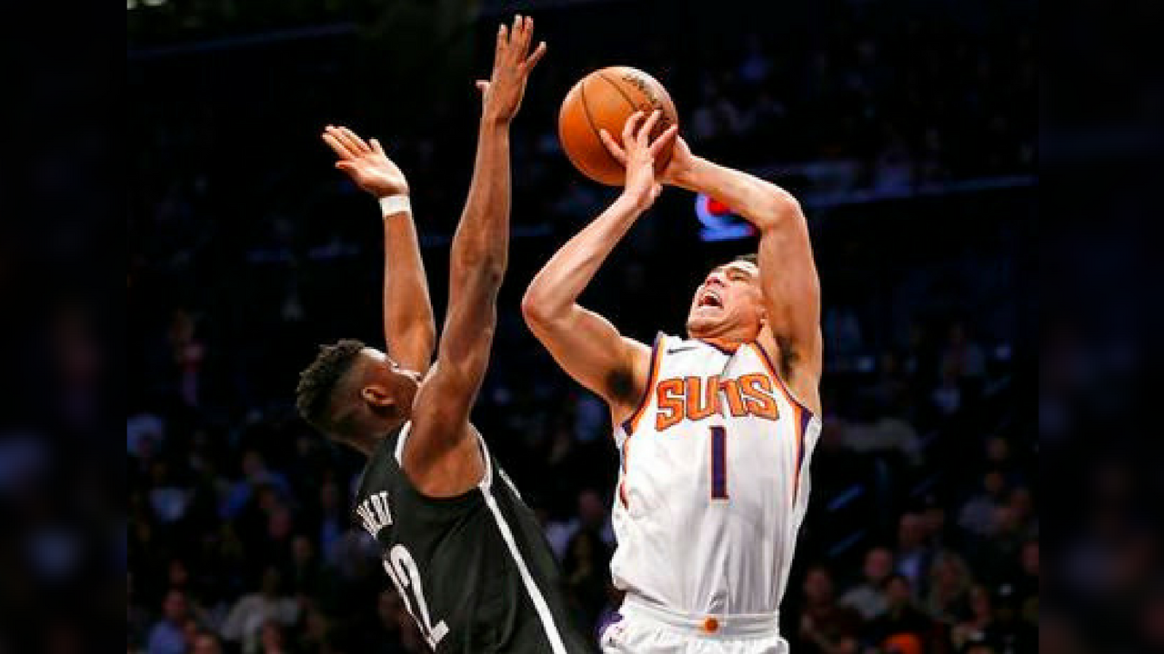 Brooklyn Nets guard Caris LeVert (22) defends Phoenix Suns guard Devin Booker (1) who loses control of the ball while shooting for two points in the second half. (Source: AP Photo/Kathy Willens)