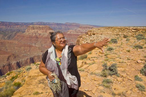 This April 7, 2015. photo provided by Tom Bean shows Renae Yellowhorse, a spokesperson for Save the Confluence, at Confluence Overlook on the East Rim of the Grand Canyon on Navajo Nation west of The Gap, Ariz.,(Tom Bean via AP)