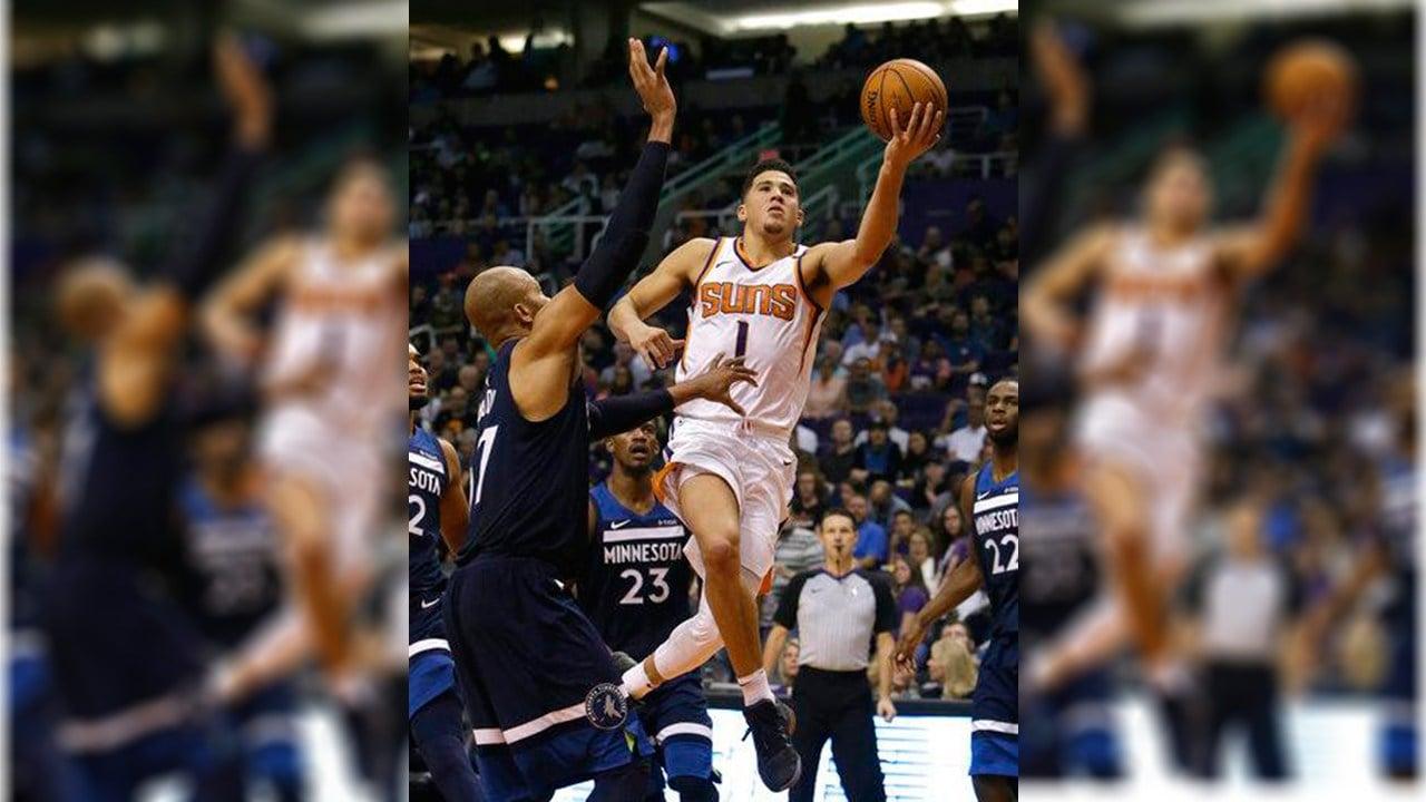Phoenix Suns guard Devin Booker (1) drives on Minnesota Timberwolves forward Taj Gibson in the second half during an NBA basketball game, Saturday, Nov 11, 2017, in Phoenix. The Suns defeated the Timberwolves 118-110. (Source: AP Photo/Rick Scuteri)