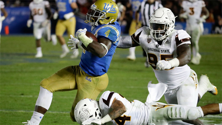 UCLA running back Bolu Olorunfunmi runs against the ASU defense (AP Photo/Chris Carlson)