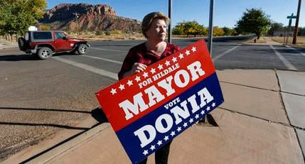 In this Thursday, Oct. 26, 2017 photo, Donia Jessop holds her mayoral campaign sign outside her store in Colorado City, Ariz.(Source: AP Photo/Rick Bowmer)