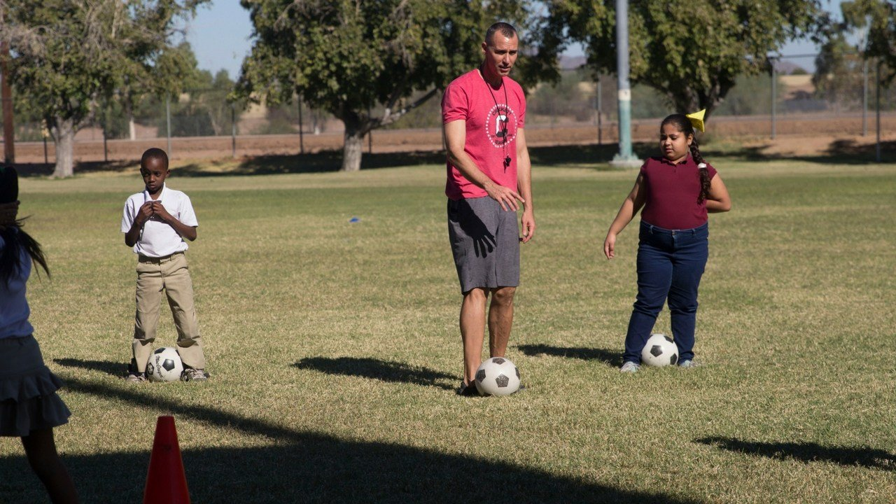 Josh Meibos tells students to kick a soccer ball with the inside of their foot. (Photo by Paola Garcia/Cronkite News)