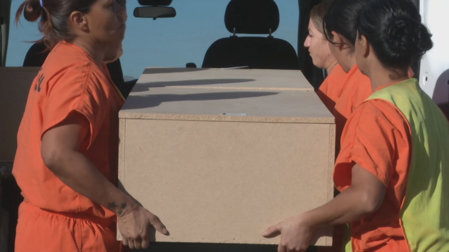 Inmates help move the casket from the van to the ground. (Source: 3TV/CBS 5)