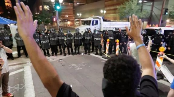Protesters raise their hands after Phoenix police used tear gas outside the Phoenix Convention Center, Tuesday, Aug. 22, 2017, in Phoenix. Protests were held against President Trump as he hosted a rally inside the convention center.  (AP Photo/Matt York)