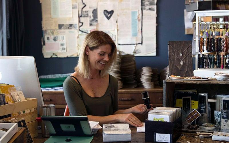 Bunky Boutique's merchandiser, Lauren Booth, stamps paper bags in preparation for Black Friday weekend. (Source: Alyssa Williams/Cronkite News)
