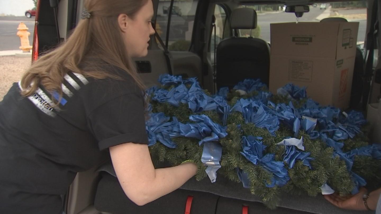 Erin Morgan loads a wreath into a car. 27 Nov. 2017 (Source: 3TV/CBS 5 News)
