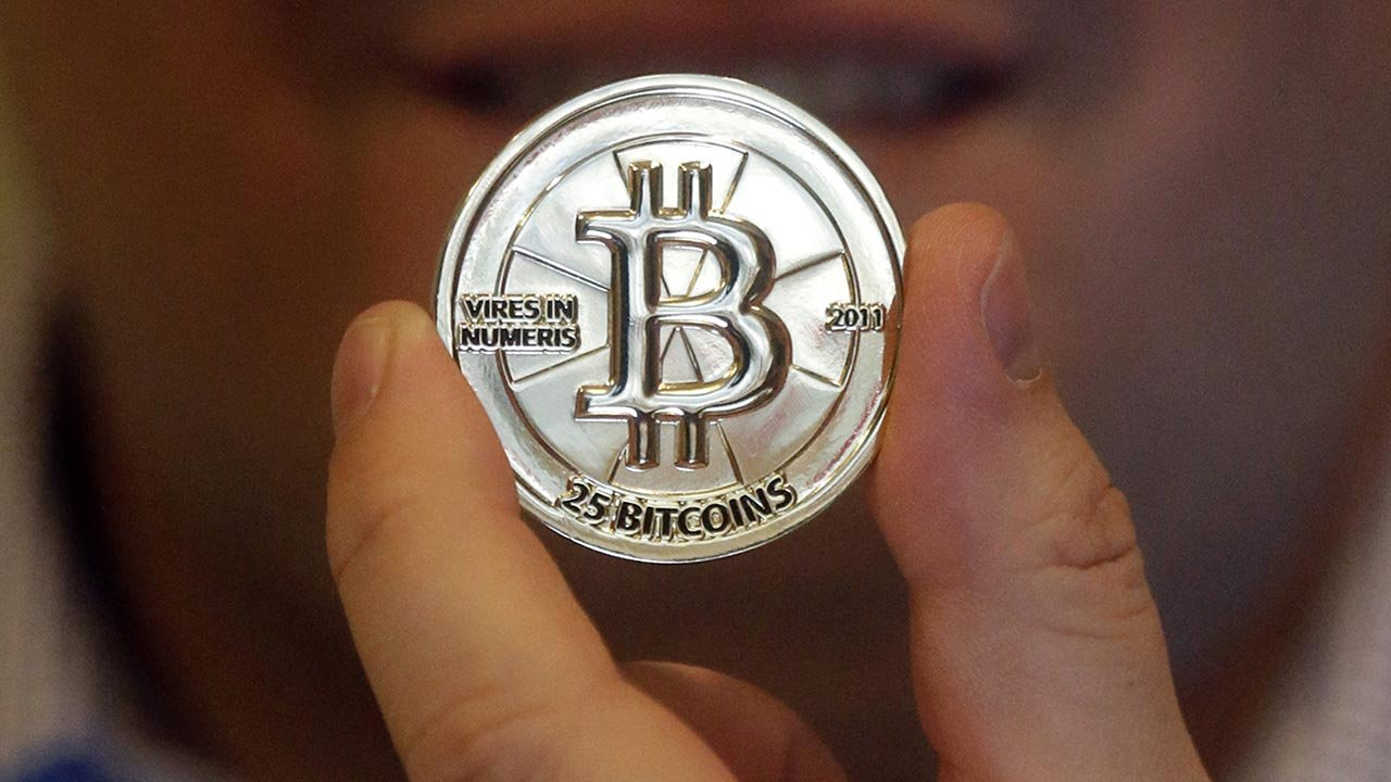 In this April 3, 2013 photo, Mike Caldwell, a software engineer, holds a 25 Bitcoin token at his shop in Sandy, Utah. Bitcoin is an online currency that does not involve banks, credit card issuers or other third parties.(SOURCE: AP Photo/Rick Bowmer)