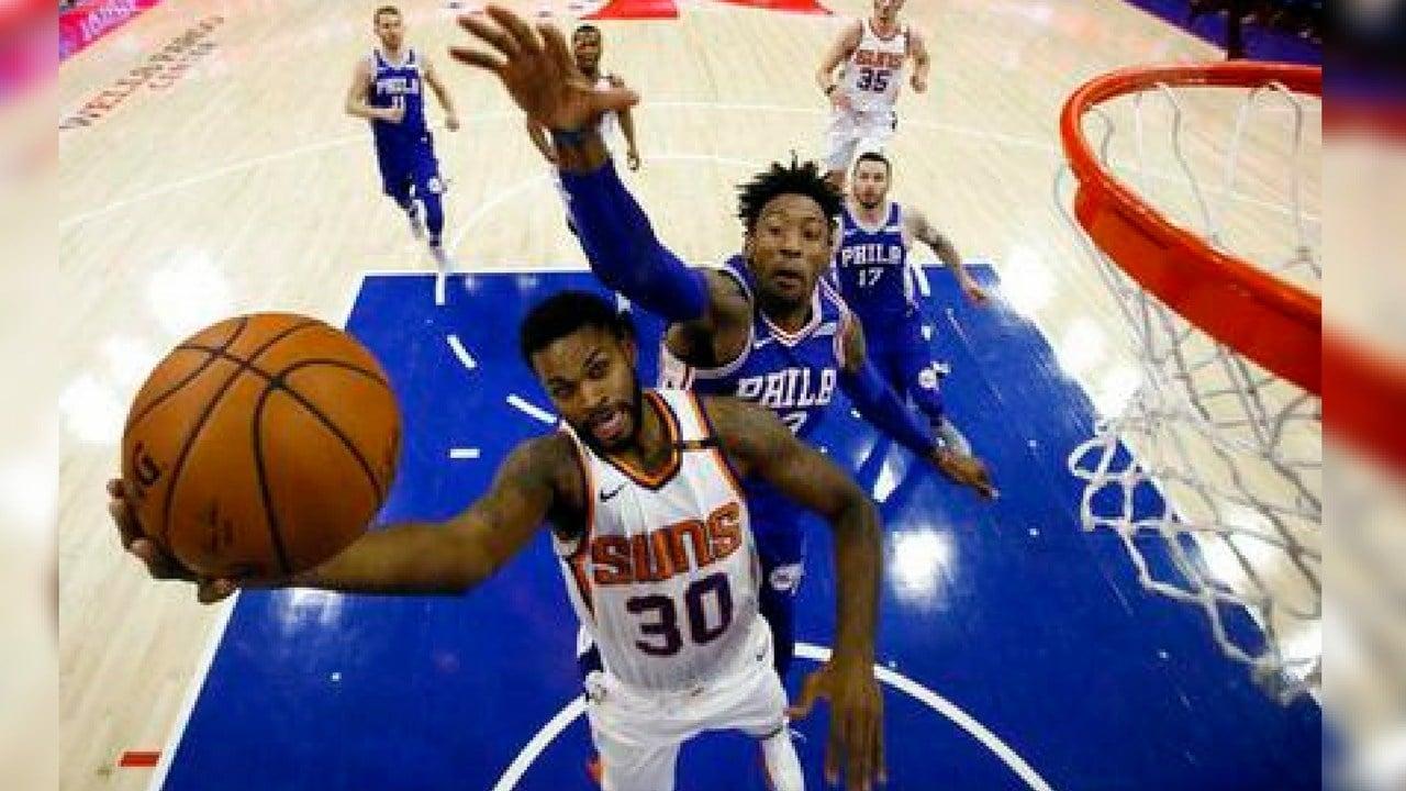 Phoenix Suns' Troy Daniels, left, goes up to shoot against Philadelphia 76ers' Robert Covington during the first half of an NBA basketball game, Monday, Dec. 4, 2017, in Philadelphia. (AP Photo/Matt Slocum)