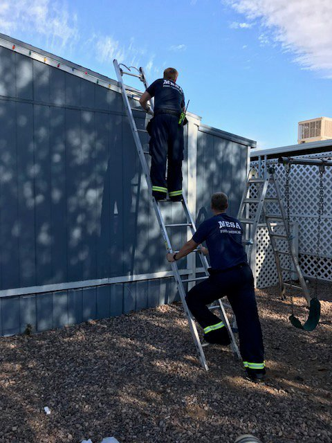 Firefighters showed proper ladder safety while putting up the lights. (Source: Mesa Fire & Medical Dept.)