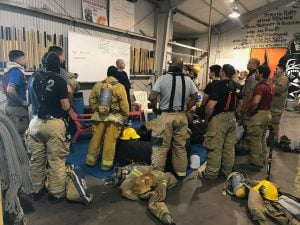 Firefighters huddle for a talk at an exercise gym before starting their session. (Source: Sydney Isenberg/Cronkite News)