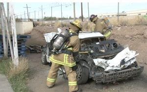 Firefighters pound on a car to practice accuracy when wielding an axe at a Phoenix gym that helps keep firefighters in shape. (Source: Sydney Isenberg/Cronkite News)