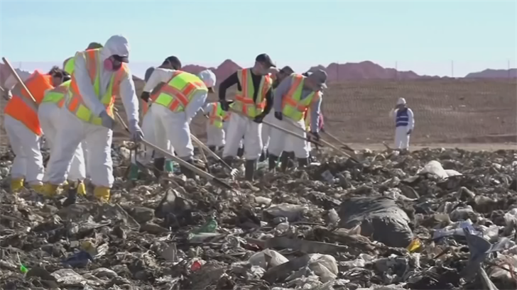 Video previously released by police showed dozens of searchers wearing rubber boots and protective clothing and face masks using long-tined rakes to examine material excavated from the landfill by a power shovel. (Source: Phoenix Police Department)