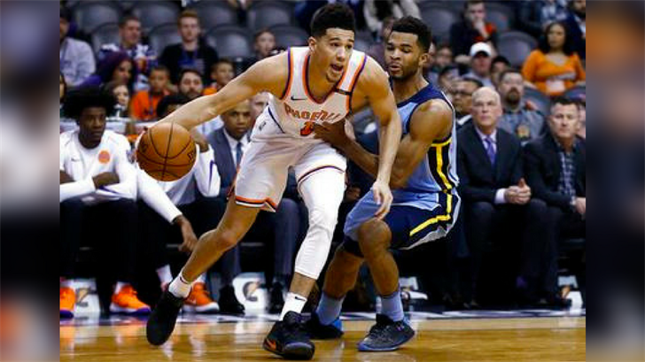 Back from injury, Phoenix Suns guard Devin Booker (1) dribbles past Memphis Grizzlies guard Andrew Harrison, right, during the first half of an NBA basketball game, Tuesday, Dec. 26, 2017, in Phoenix. (Source: AP Photo/Ross D. Franklin)