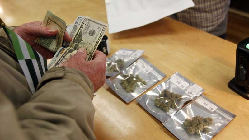 A customer purchases marijuana at Harborside marijuana dispensary in Oakland, CA. As of Jan. 1, 2018, recreational pot can be sold legally in California. (Source: AP Photo/Mathew Sumner)