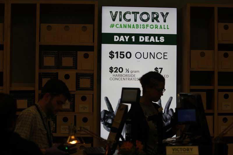 A lighted sign advertises deals at Harborside marijuana dispensary in Oakland, CA on Jan. 1, 2018. (Source: AP Photo/Mathew Sumner)