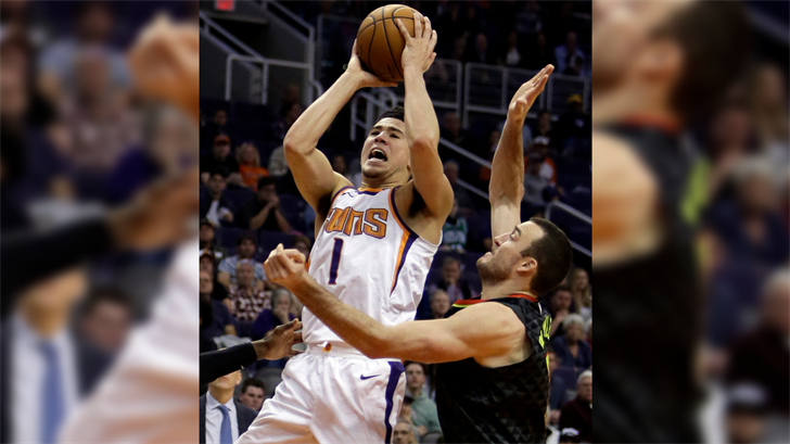 Phoenix Suns guard Devin Booker (1) drives on Atlanta Hawks guard Marco Belinelli during the second half of an NBA basketball game Tuesday, Jan. 2, 2018, in Phoenix. The Suns defeated the Hawks 104-103. (Source: AP Photo/Rick Scuteri)