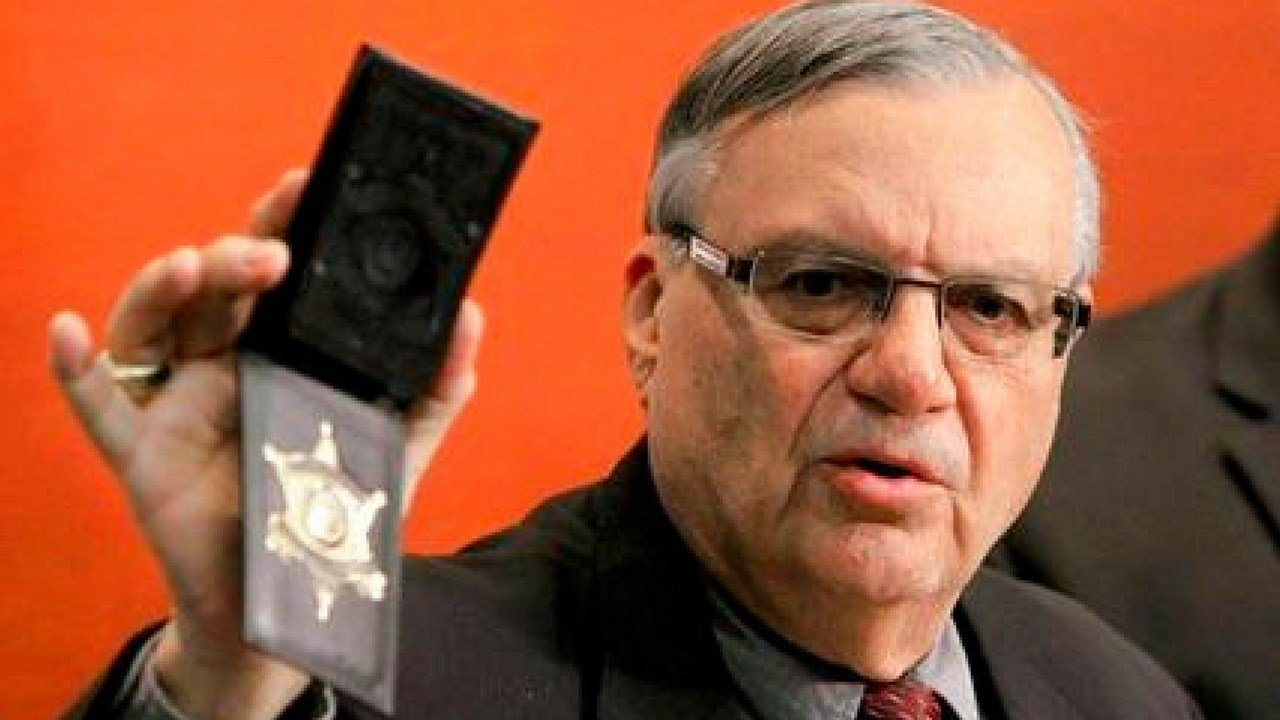 FILE- In this Dec. 21, 2011 file photo, Maricopa County Sheriff Joe Arpaio shows his badge as he holds a ceremony where 92 of his immigration jail officers.(AP Photo/Ross D. Franklin, File)