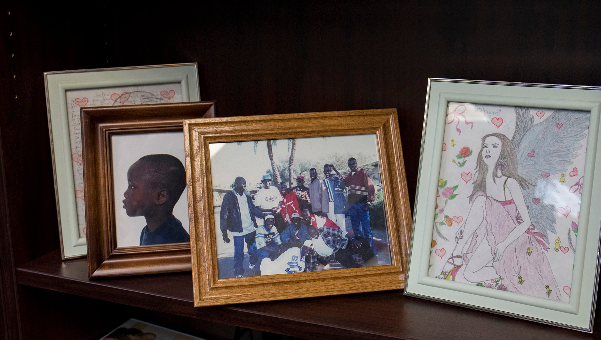 Some of the earliest refugee children in Arizona were young men fleeing the Sudan. Their photos sit on a bookshelf in the Catholic Charities office. (Nicole Tyau/Cronkite News)