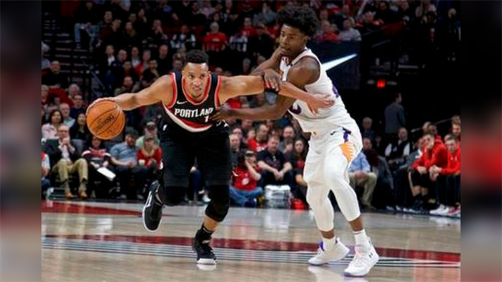 Portland Trail Blazers guard Evan Turner, left, dribbles past Phoenix Suns forward Josh Jackson during the first half of an NBA basketball game in Portland, Ore., Tuesday, Jan. 16, 2018. (Source: AP Photo/Craig Mitchelldyer)