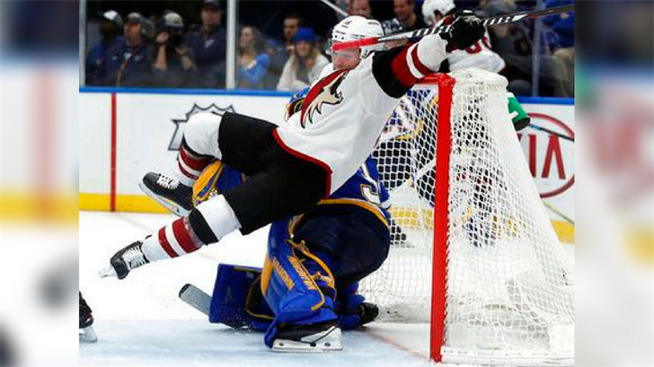 Arizona Coyotes' Max Domi, top, falls over St. Louis Blues goaltender Jake Allen during the third period of an NHL hockey game Saturday, Jan. 20, 2018, in St. Louis. (Source: AP Photo/Jeff Roberson)