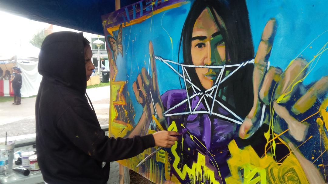 Artist Jules Badoni with artwork. (Source: AAITA)
